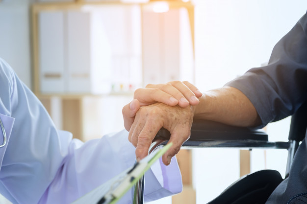 doctor-sosteniendo-mano-paciente-anciano-silla-ruedas_28914-454
