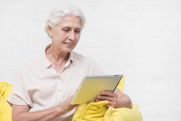 feliz-mujer-senior-mirando-tableta-digital-contra-pared-blanca_23-2147861629