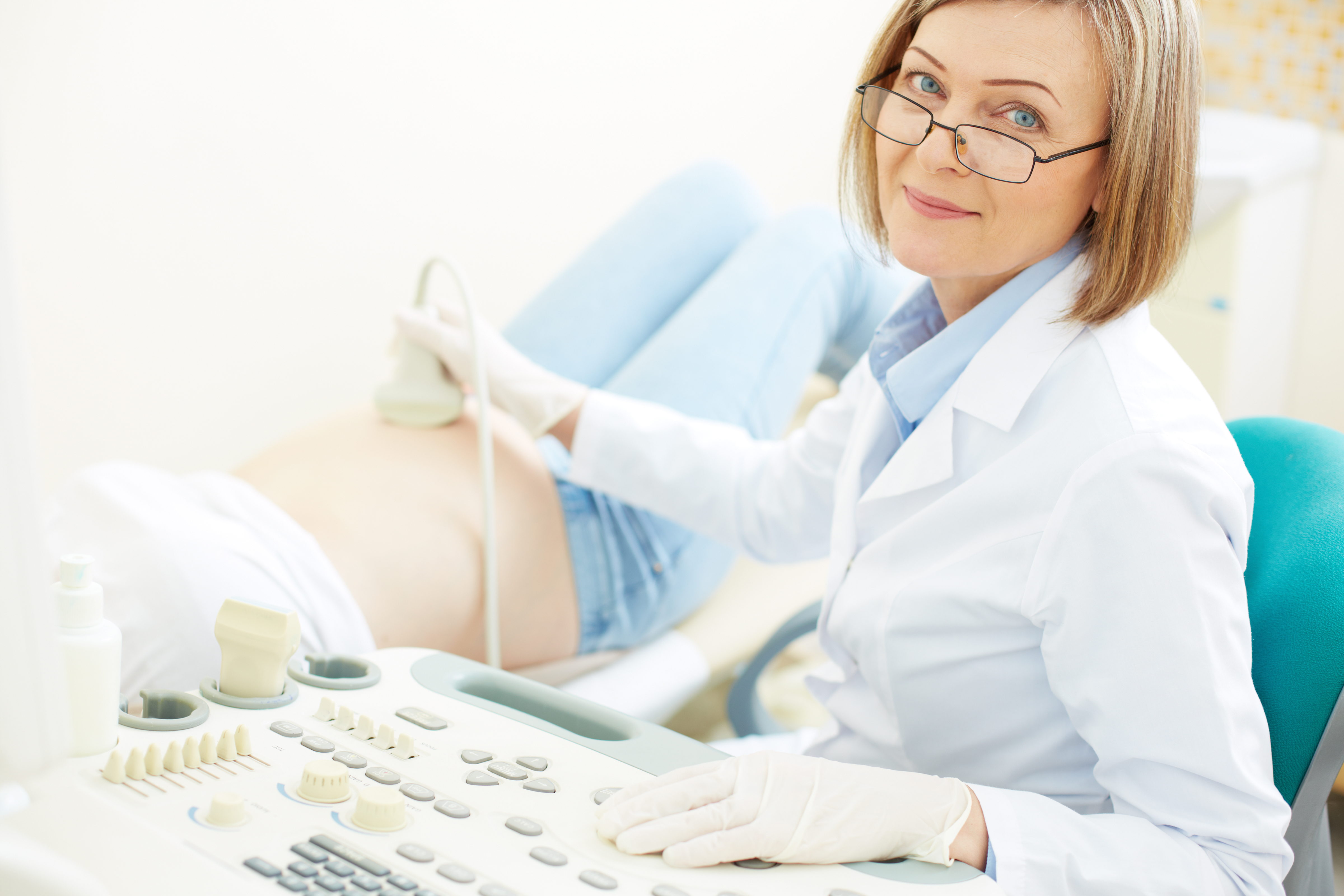 Mature doctor making an ultrasound examination to pregnant woman