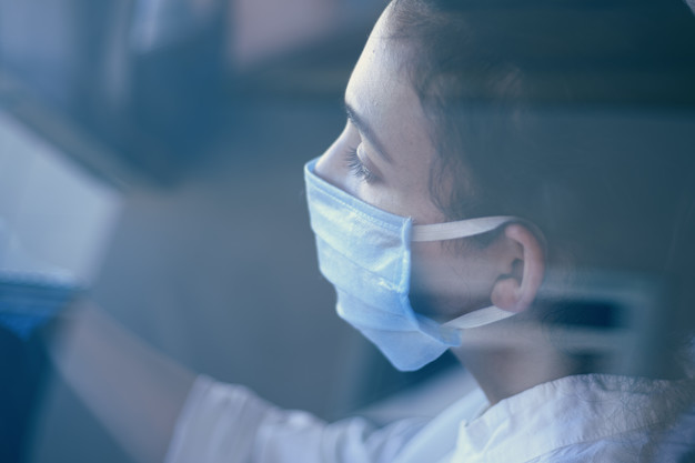 A young woman in a surgical face mask and gloves driving the car during coronavirus pandemic. A female driver in protective gear, preventing infection of covid-19 virus
