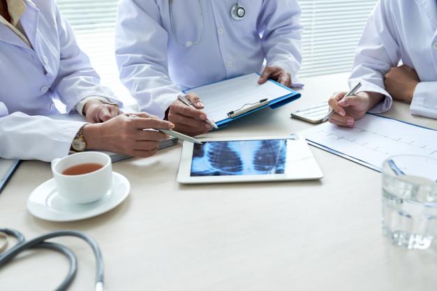 tres-medicos-recortados-que-analizan-radiografia-torax-teclado-digital_1098-18899