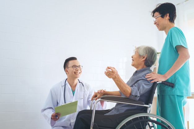 doctor-sosteniendo-mano-paciente-anciano-silla-ruedas_28914-452