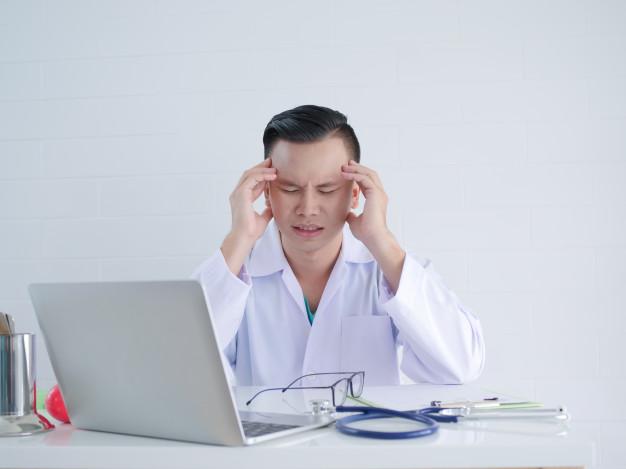 doctor-joven-dolor-cabeza-trabajo_1286-964