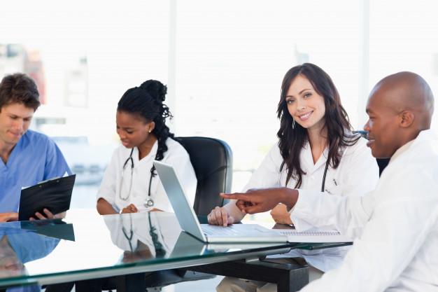 dos-medicos-pasantes-sonrientes-que-trabajan-computadora-cerca-colegas_13339-206215