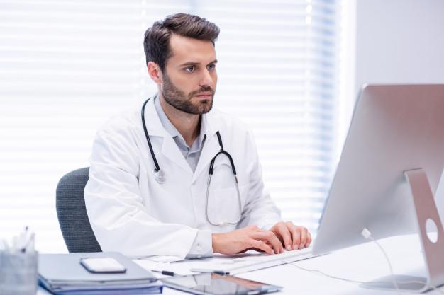 medico-masculino-trabalhando-no-computador-pessoal_107420-66926